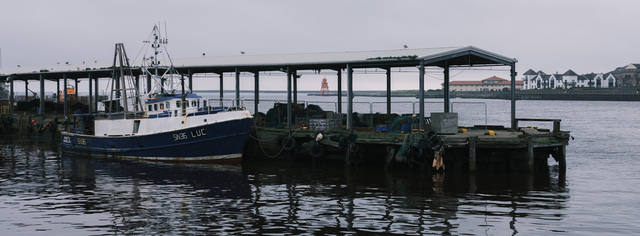 A fishing boat is moored to a wharf at North Shields fish quay on a grey day